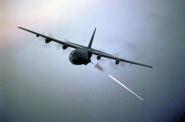 An air-to-air left front view of an AC-130 Hercules aircraft during target practice.
